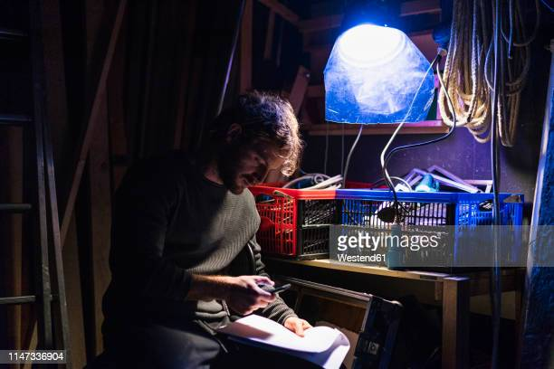 man with script sitting backstage at theatre looking at cell phone - backstage stock pictures, royalty-free photos & images