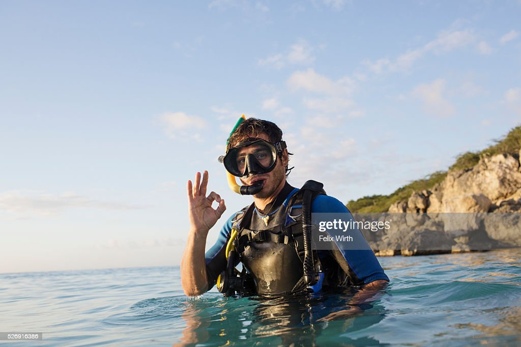 Man with scuba diving equipment in sea showing ok sign : Stockfoto