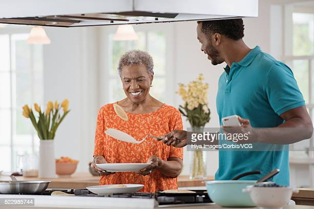 Man with senior mother cooking pancakes in kitchen