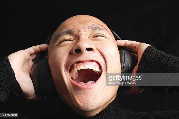man with shaved head, wearing headphones, mouth open - uvula stock photos and pictures