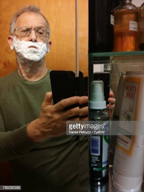 Man With Shaving Cream On Face Photographing Through Mobile Phone In Bathroom