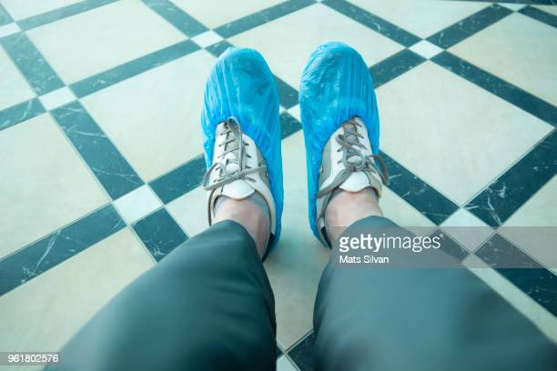 man with shoe protector - shoe covers stock pictures, royalty-free photos & images