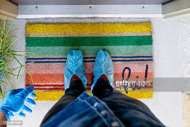 man with shoe protectors and gloves standing on door mat in at home doorway - shoe covers stock pictures, royalty-free photos & images