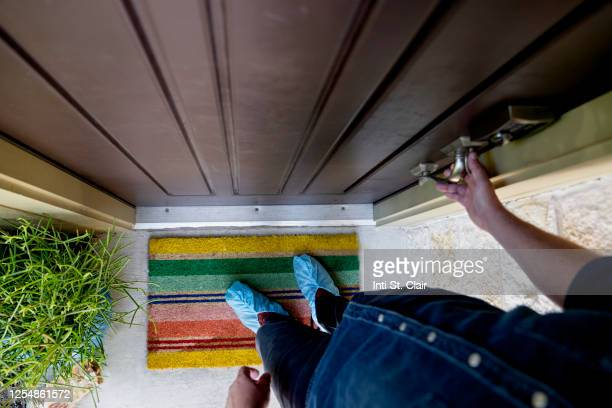 man with shoe protectors entering front door of home - shoe covers stock pictures, royalty-free photos & images