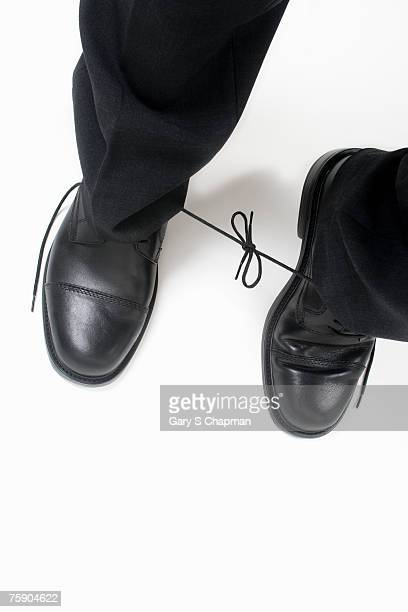 Man with shoelaces tied together, low section, high angle view