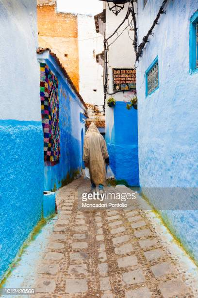 Man with shopping bags in an alley of Chefchaouen April 2018