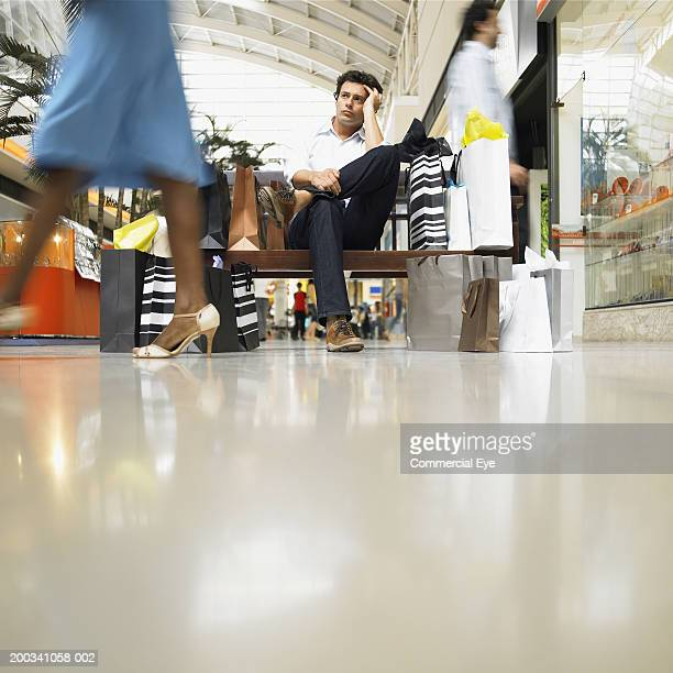 Man with shopping bags sitting on bench in mall, ground view