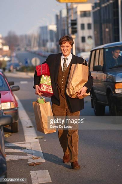 Man with shopping bags walking down street