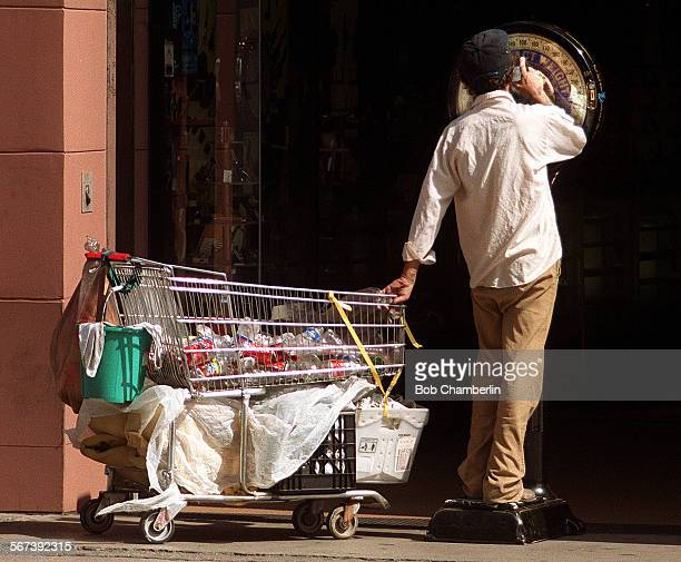 Man with shopping cart partially filled with plastic bottles and cans takes a whimsical moment to check his own weight on a scale in front of store...