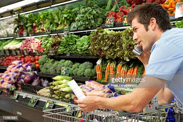 Man with shopping list in supermarket, using mobile phone