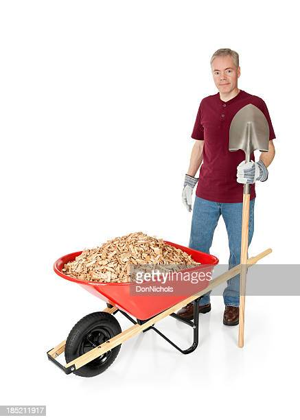 Man with Shovel and a Wheelbarrow Full of Mulch