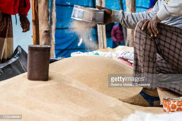 man with sieve for cereals in bati market, ethiopia, africa - アフリカの角 ストックフォトと画像