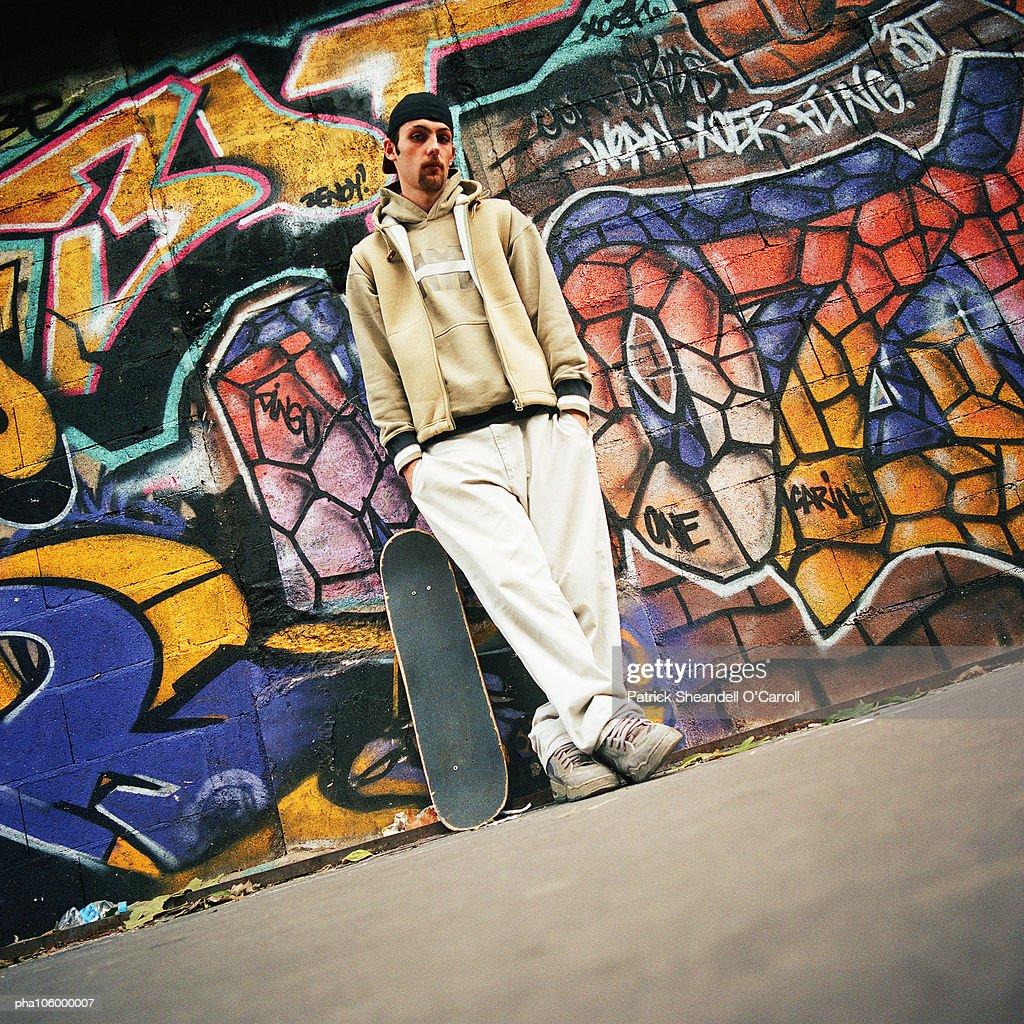 Man with skateboard leaning against graffiti wall, portrait : Stockfoto