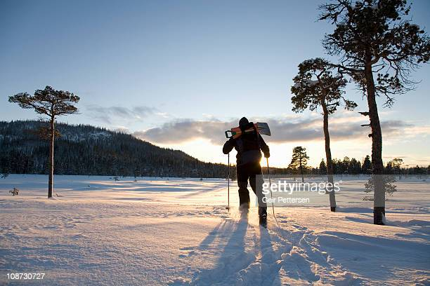 Man with skis and backpack in the low winter sun