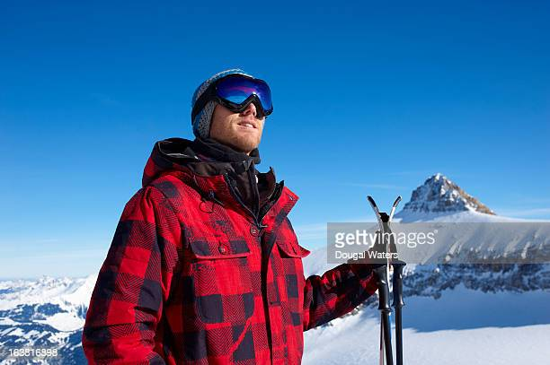A man with skis in a snowy landscape.