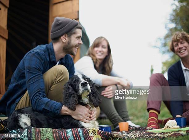 Man with small dog sitting outside yurt.