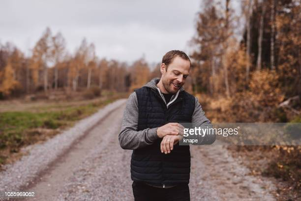 man with smart fitness watch tracker outdoors walking in nature - fitness tracker stock pictures, royalty-free photos & images