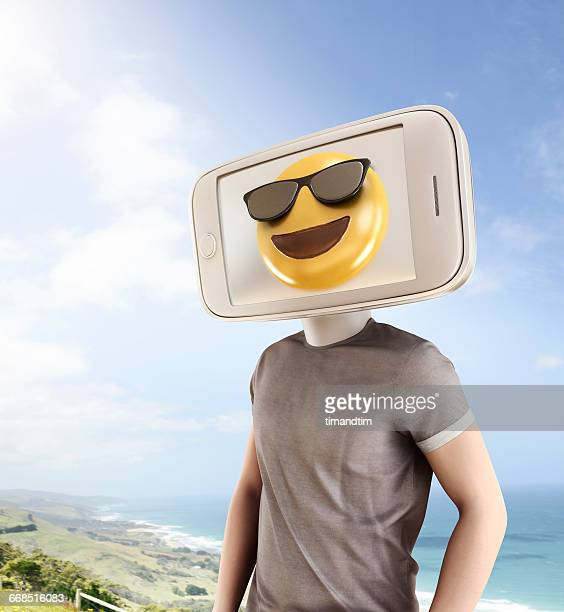 Man with Smartphone and a happy emoji on the beach