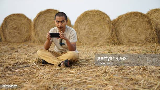 man with smartphone at haystack - shaifulzamri photos et images de collection