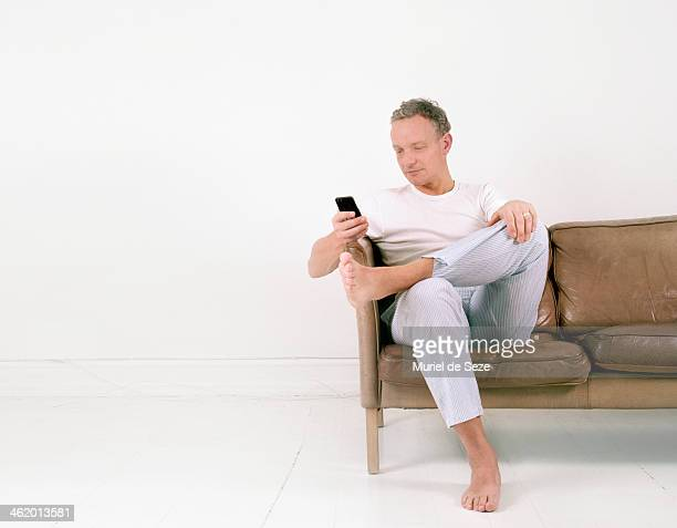 Man with smartphone on sofa