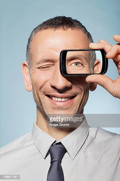 Man with smartphone over eye