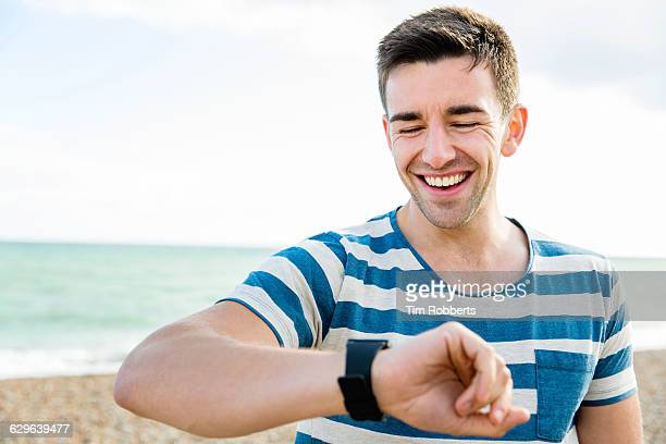 Man with smartwatch on beach.