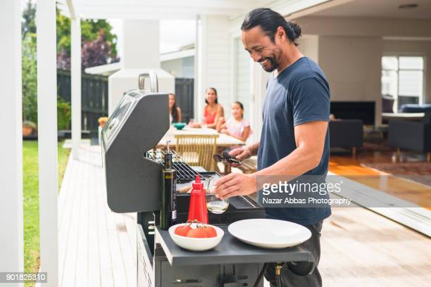 man with smile on his face preparing barbecue for family. - mid adult men stock pictures, royalty-free photos & images