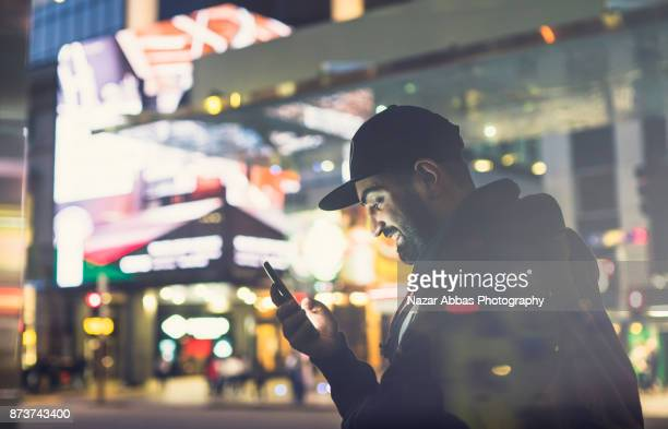 Man with smile on his face using smartphone in urban street.