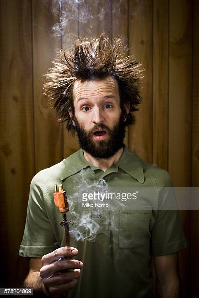 Man with smoking hair and electrical plug