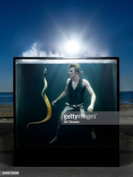 Man with snake in water tank