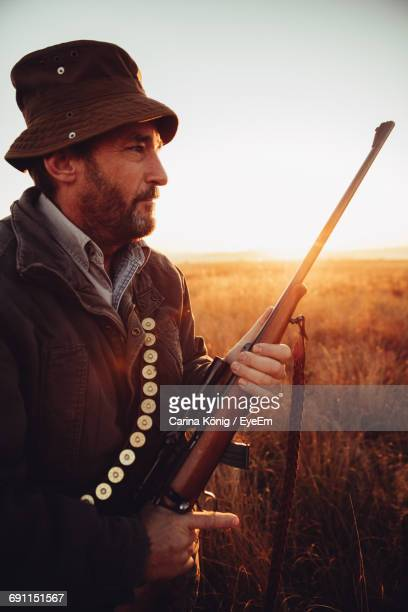 Man With Sniper Standing On Field Against Sky
