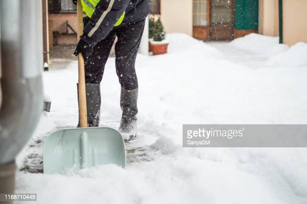man with snow shovel cleans sidewalk - digging stock pictures, royalty-free photos & images