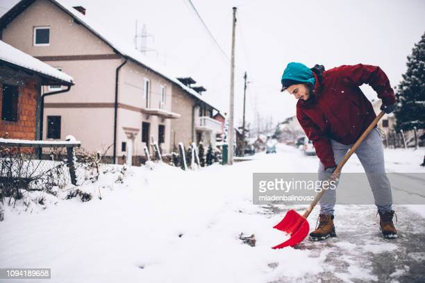 man with snow shovel - snow shovel stock photos and pictures