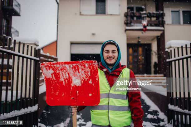 man with snow shovel - snow shovel stock pictures, royalty-free photos & images