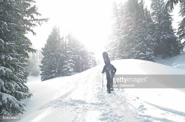 man with snowboard hiking up mountain - dan sherwood photography stock pictures, royalty-free photos & images