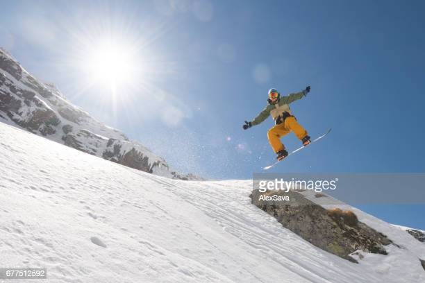 Man with snowboard jumping in midair on steep slope