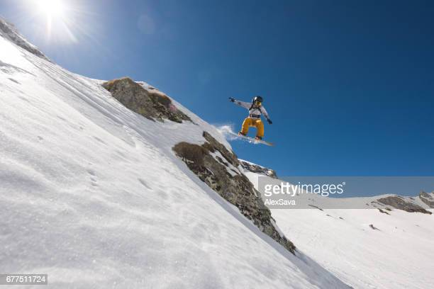 Man with snowboard jumping in midair while riding off piste