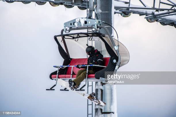 man with snowboard sitting on a ski lift - one man only stock pictures, royalty-free photos & images