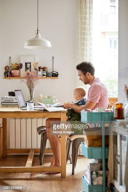 man with son analyzing documents at table - mid adult men foto e immagini stock
