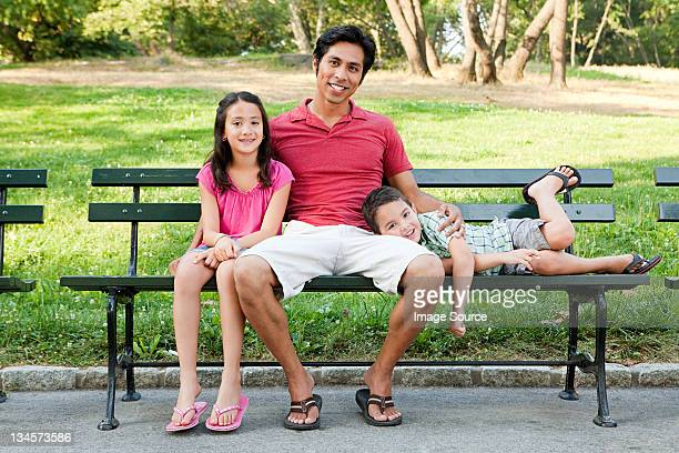 Man with son and daughter on park bench, portrait