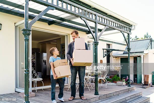 Man with son holding boxes while standing at porch