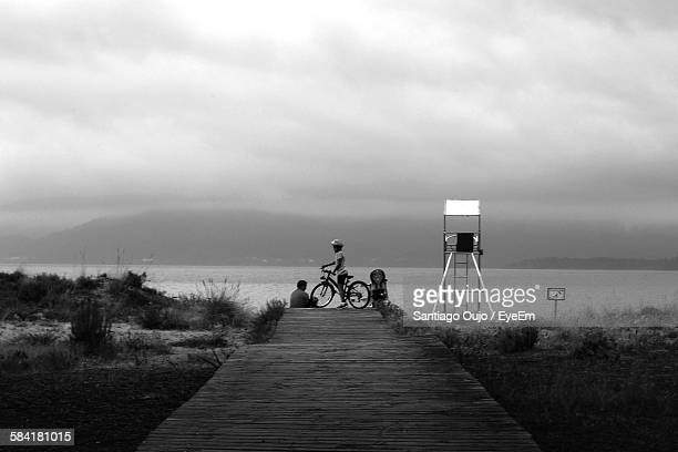 Man With Son Riding Bicycle On Pier At Beach Against Cloudy Sky