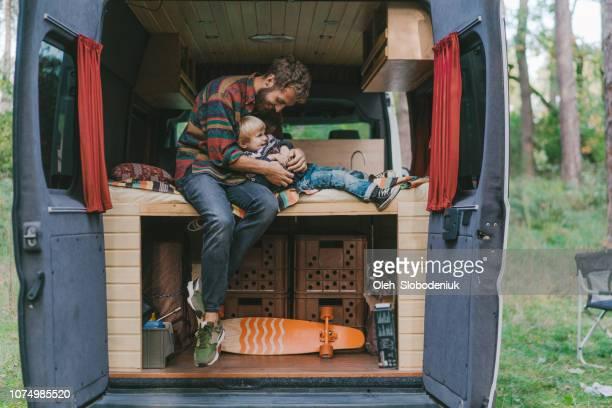 man met zoon zit in kampeerauto - camper stockfoto's en -beelden