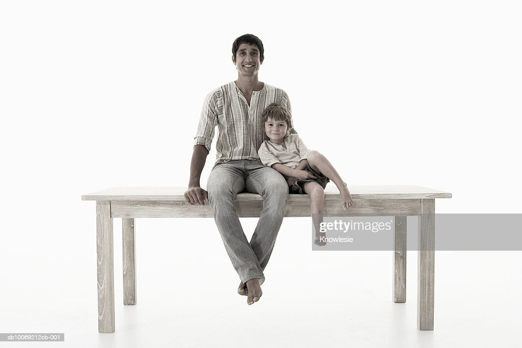 Man with son (4-5 years) sitting on table against white background, portrait : Stockfoto