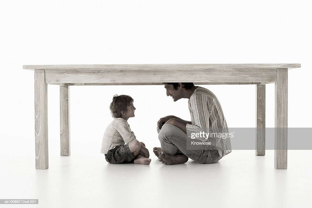 Man with son (4-5 years) sitting under table, studio shot : Stockfoto