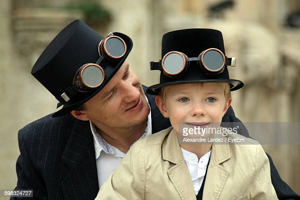 Man With Son Wearing Old-Fashioned Goggles On Hat
