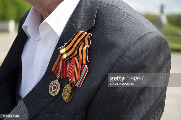 A man with Sovietera medals poses for photos at the Soviet War Memorial at Treptower Park in Berlin as people pay their respects on VE day marking...