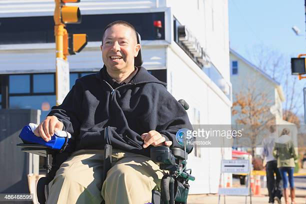 Man with spinal cord injury and arm with nerve damage in motorized wheelchair crossing public street while shopping