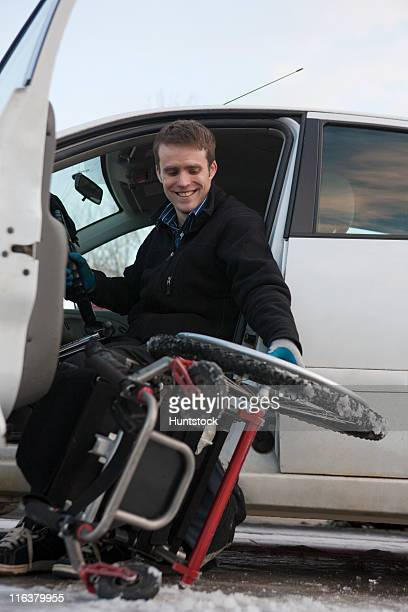 Mann mit Verletzungen disassembling Rückenmark dem Rollstuhl zu erhalten