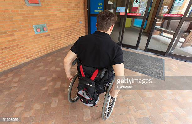 Man with spinal cord injury entering electronic door